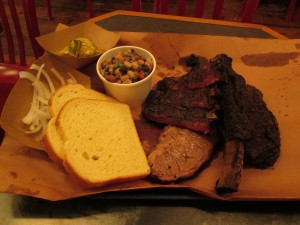 (clockwise): pork ribs, beef rib, and brisket with onions, pickles, Texas caviar, and white bread