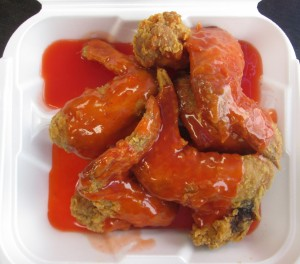 fried chicken wings slathered with a neon mumbo sauce at Wing Wah