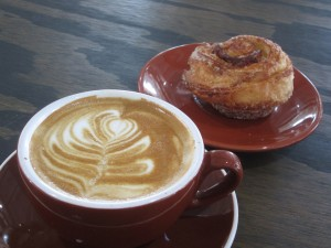 a flat white with a cinnamon roll by Frenchies