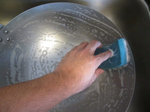 washing the interior of the wok with soap and water using a downward spiral