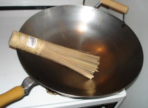 a wok with traditional scrub brush with bamboo bristles (photo courtesy of W.K. Leung)